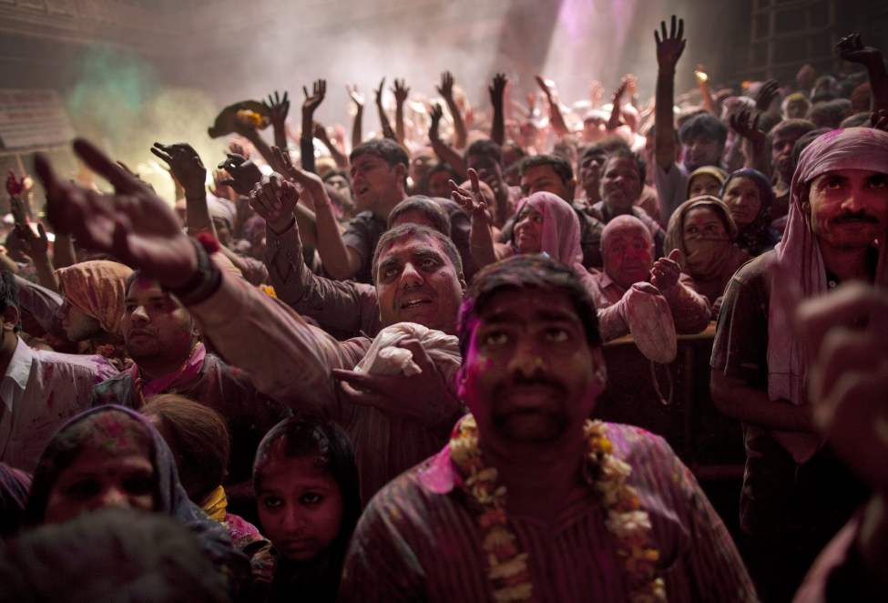 Hindu devotees crowd and reach for sweets as they face a deity while celebrating Holi,  the festival of color, at the Banke Bihari temple in Vrindavan, about 140 kilometers (87 miles) from New Delhi, India, Thursday, March 8, 2012. Vrindavan is a famous place for Holi celebrations, where according to legend, the Hindu god Krishna played Holi with his consort Radha. (AP Photo/Kevin Frayer) (CP)