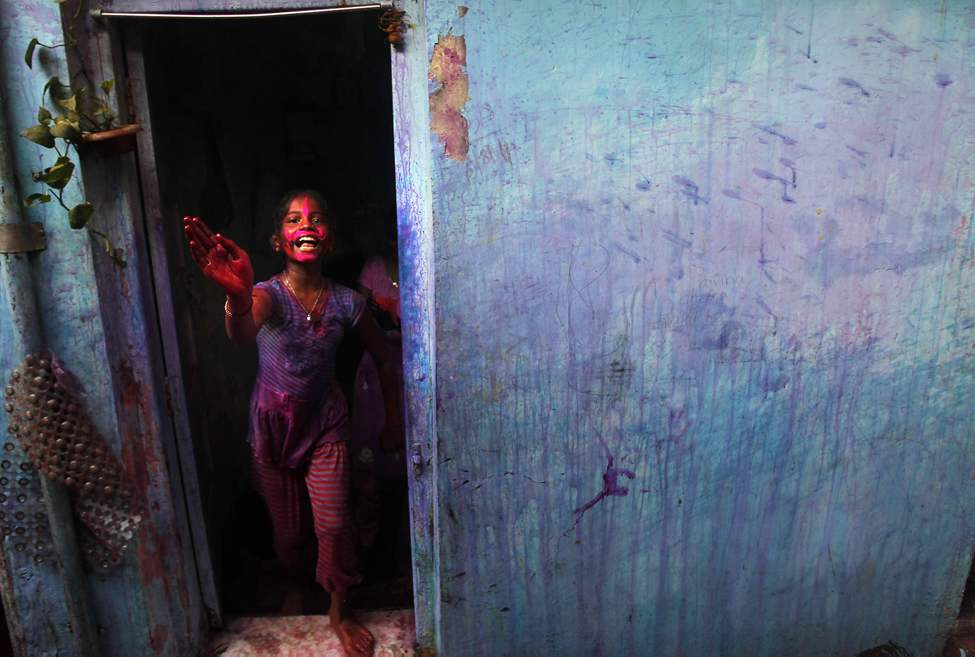 An Indian girl, her face smeared with colored powder, looks out from her house during Holi celebrations in Mumbai, India, Thursday, March 8, 2012. Holi, the Hindu festival of colors, also heralds the coming of spring. (AP Photo/Rafiq Maqbool)