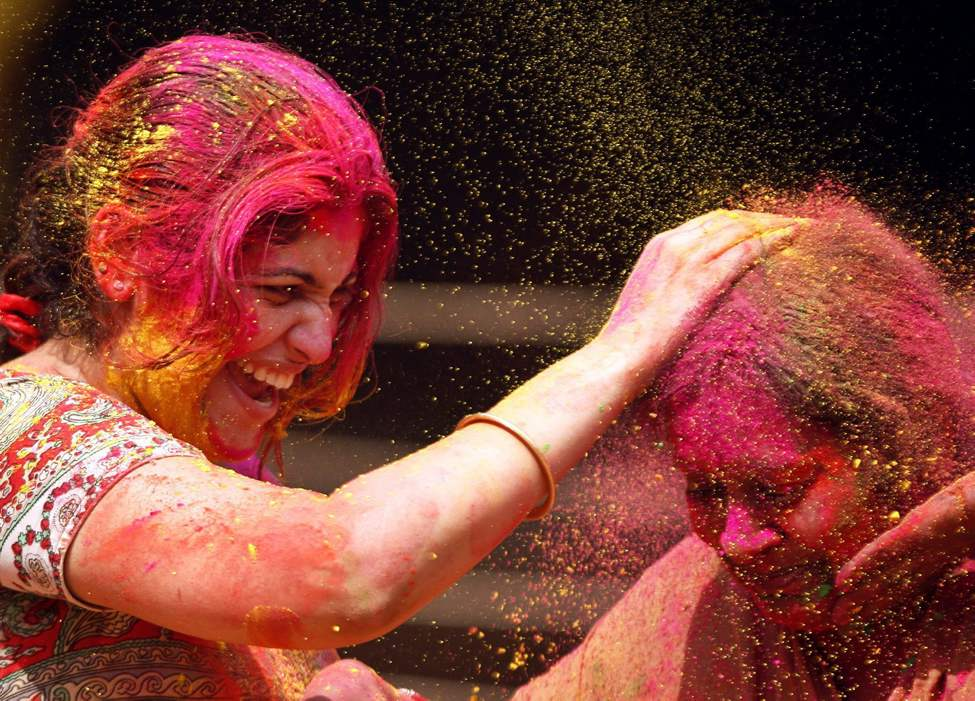 Indian women smear colored powder on each other during Holi celebrations in Chennai, India, Thursday, March 8, 2012. Holi, the Hindu festival of colors, also heralds the coming of spring. (AP Photo/Arun Sankar K.)