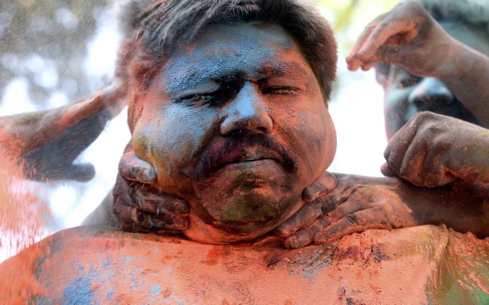 A man reacts as his face is smeared with colored powder by friends during Holi festivities in Mumbai, India, Thursday, March 8, 2012. Holi, the Hindu festival of colors, also heralds the coming of spring. (AP Photo/ Rajanish Kakade)