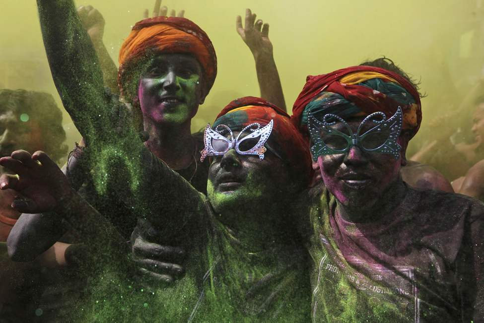 Indian men, their faces smeared with colored powder, dance during Holi celebrations in Gauhati, India, Thursday, March 8, 2012. Holi, the Hindu festival of colors, also heralds the coming of spring. (AP Photo/Anupam Nath) (CP)