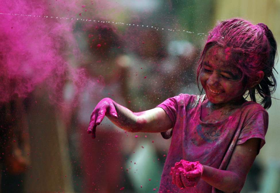 An Indian girl, her face smeared with colored powder, reacts as water is squirted on her during Holi celebrations in Chennai, India, Thursday, March 8, 2012. Holi, the Hindu festival of colors, also heralds the coming of spring. (AP Photo/Arun Sankar K.) (CP)