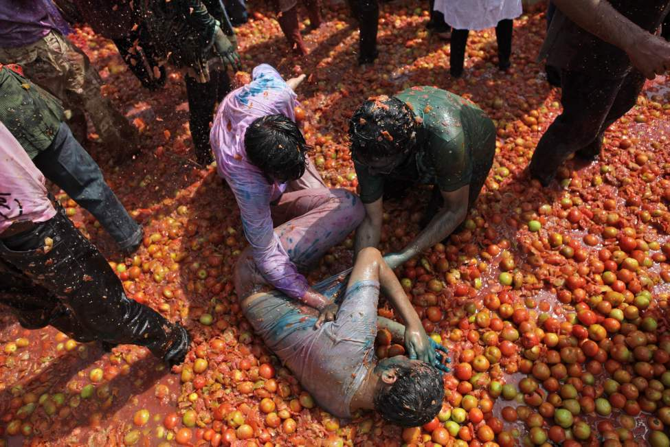 Indian men dunk a friend in tomato slush during Holi celebrations in Gauhati, India, Thursday, March 8, 2012. Holi, the Hindu festival of colors, also heralds the coming of spring. (AP Photo/Anupam Nath)