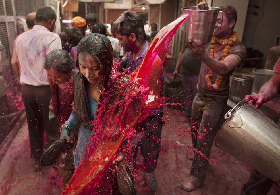 A Hindu devotee has a bucket of coloured water poured on her whilst walking to the the Banke Bihari temple to celebrate