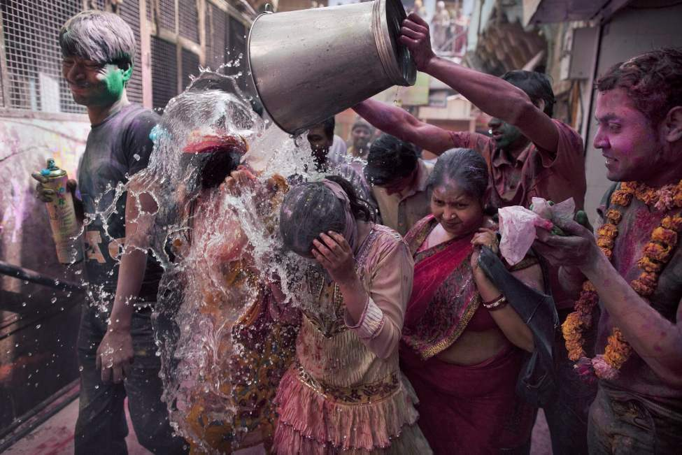 "Indian women are hit with a bucket of  water while walking to the the Banke Bihari temple to celebrate ""Holi,"" the festival of color, at  in Vrindavan, about 140 kilometers (87 miles) from New Delhi, India, Thursday, March 8, 2012. Vrindavan is a famous place for Holi celebrations, where according to legend, the Hindu god Krishna played Holi with his consort Radha. (AP Photo/Kevin Frayer) (CP)"