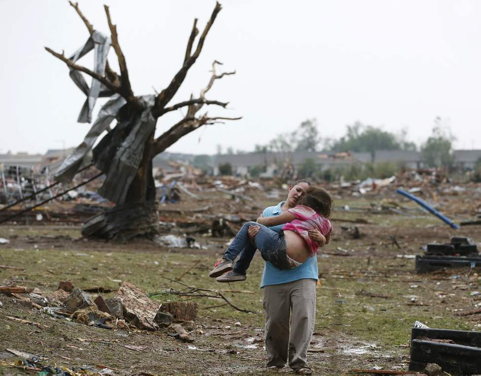 FILE - LaTisha Garcia carries her 8-year-old daughter, Jazmin Rodriguez, near Plaza Towers Elementary School, May 20, 2013, after a massive tornado carved its way through Moore, Okla., leaving little of the school and neighborhood.  (AP Photo/Sue Ogrocki, File)