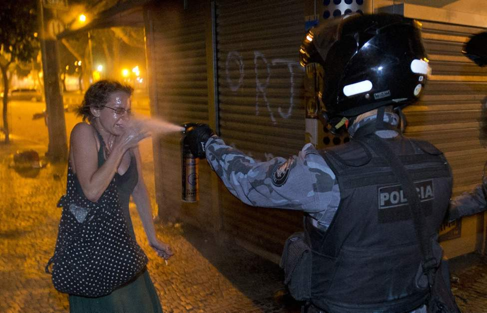 FILE - A military police peper sprays a protester during a demonstration in Rio de Janeiro, Brazil, Monday, June 17, 2013. Protesters massed in at least seven Brazilian cities for another round of demonstrations voicing disgruntlement about life in the country, raising questions about security during big events like the current Confederations Cup and the following month's Papal visit. (AP Photo/Victor R. Caivano, File)
