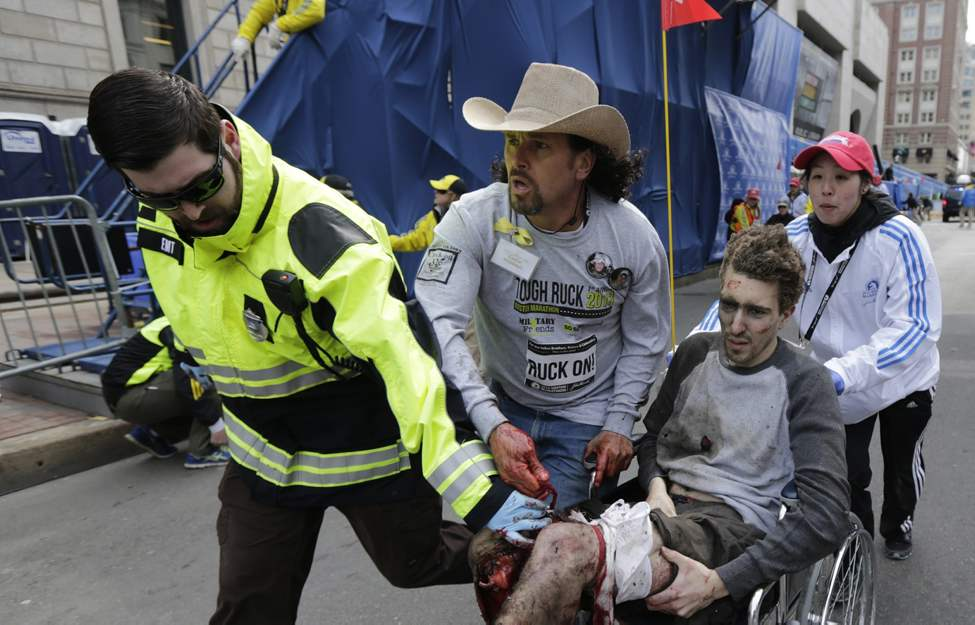 FILE - An emergency responder and volunteers, including Carlos Arredondo in the cowboy hat, push Jeff Bauman in a wheel chair after he was injured in an explosion near the finish line of the Boston Marathon Monday, April 15, 2013 in Boston. (AP Photo/Charles Krupa, File)