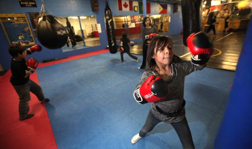 Natasha Meekis, 9, thrashes the heavy bag at GoJo Gym Tuesday during an after-school boxing program.  January 17, 2012