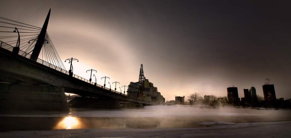 A crisp winter sun and its dog set behind the Esplanade Riel as a cold mist rises over the open Red River.  January 17, 2012