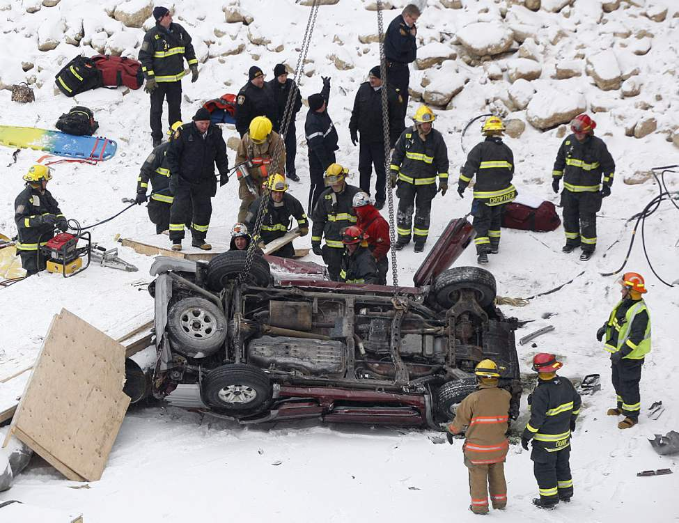 Emergency crews and construction workers evaluate the scene where a vehicle crashed through a railing on the Disraeli Bridge near Midwinter Ave. and fell on the shore of the Red River. Kaitlyn Jenna Lee Fraser, 19, died in the crash.