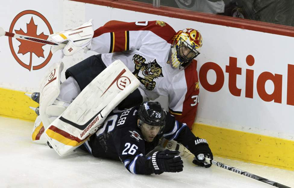 Winnipeg Jets' Blake Wheeler (26) ends up under Florida Panthers' goaltender Scott Clemmensen (30) during first period action at MTS Centre Saturday, January 21, 2012. 