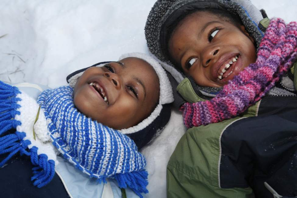 Young brothers Silla Musaka, 3 (in blue), and Manuel, 4 (green),  laugh and giggle as they play outside their home in the snow.  Their parents are from Congo and have adapted well to their new life in Canada. January 17, 2012 