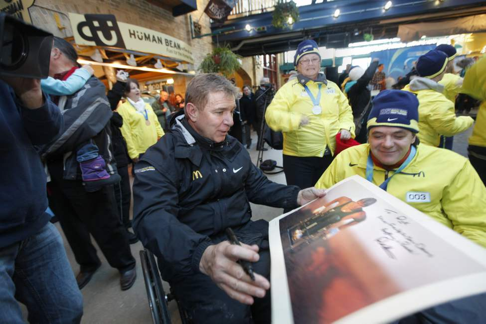 Rick Hansen signs medal bearer Rick Lafreniere's poster and book at The Forks Friday afternoon during the Man in Motion 25th Anniversary Relay.   January 20, 2012  (Ruth Bonneville /  Winnipeg Free Press)