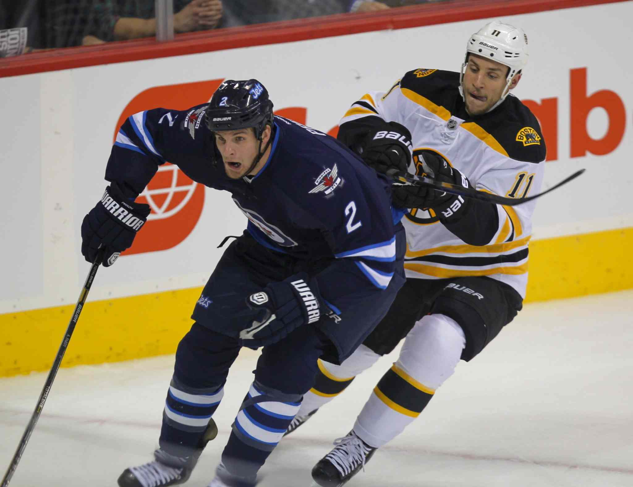 Paul Postma is chased by Gregory Campbell of the Boston Bruins in the first period.