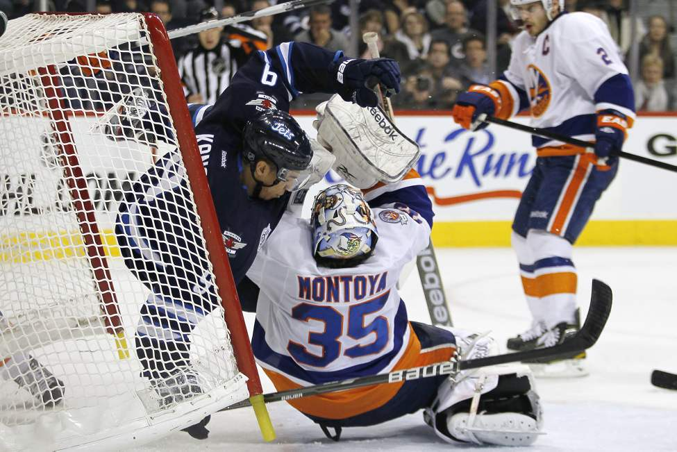 Winnipeg Jets' forward Evander Kane (9) crashes into New York Islanders goaltender Al Montoya (35) during second period NHL action in Winnipeg on December 20, 2011. (John Woods / Winnipeg Free Press)