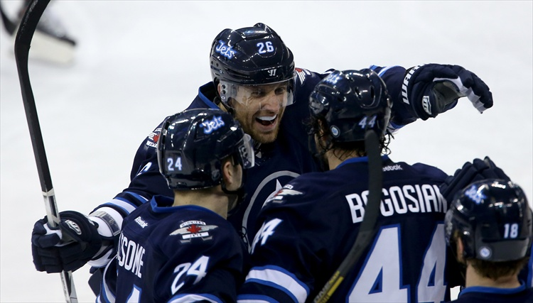 Winnipeg Jets' Blake Wheeler celebrates with Grant Clitsome and Zach Bogosian after he assisted on Bogosian's goal during the first period.