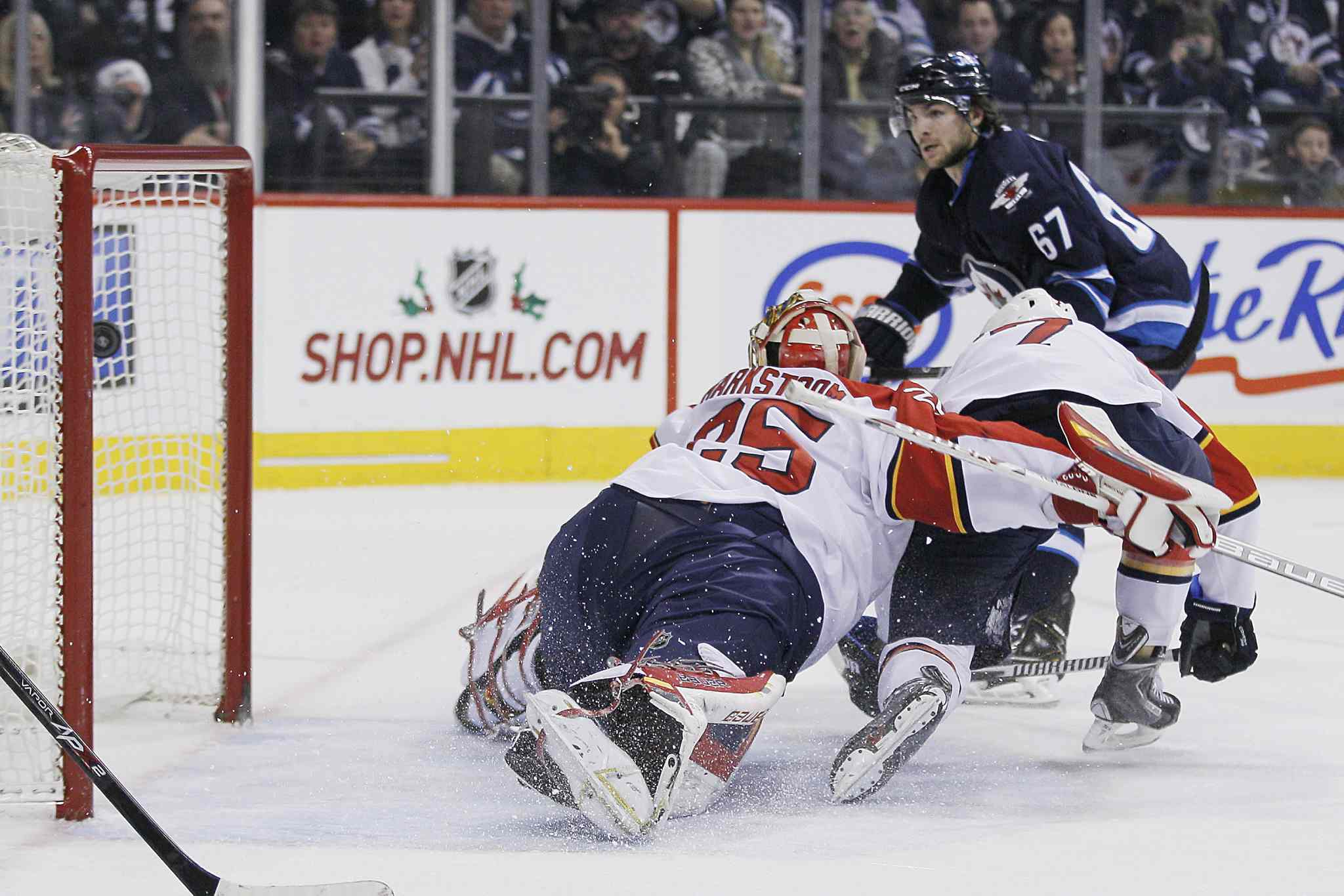 Winnipeg Jets' Michael Frolik (67) scores on Florida Panthers goaltender Jacob Markstrom (25) and Dmitry Kulikov (7) as Jets' Bryan Little (18) looks on during the second period.