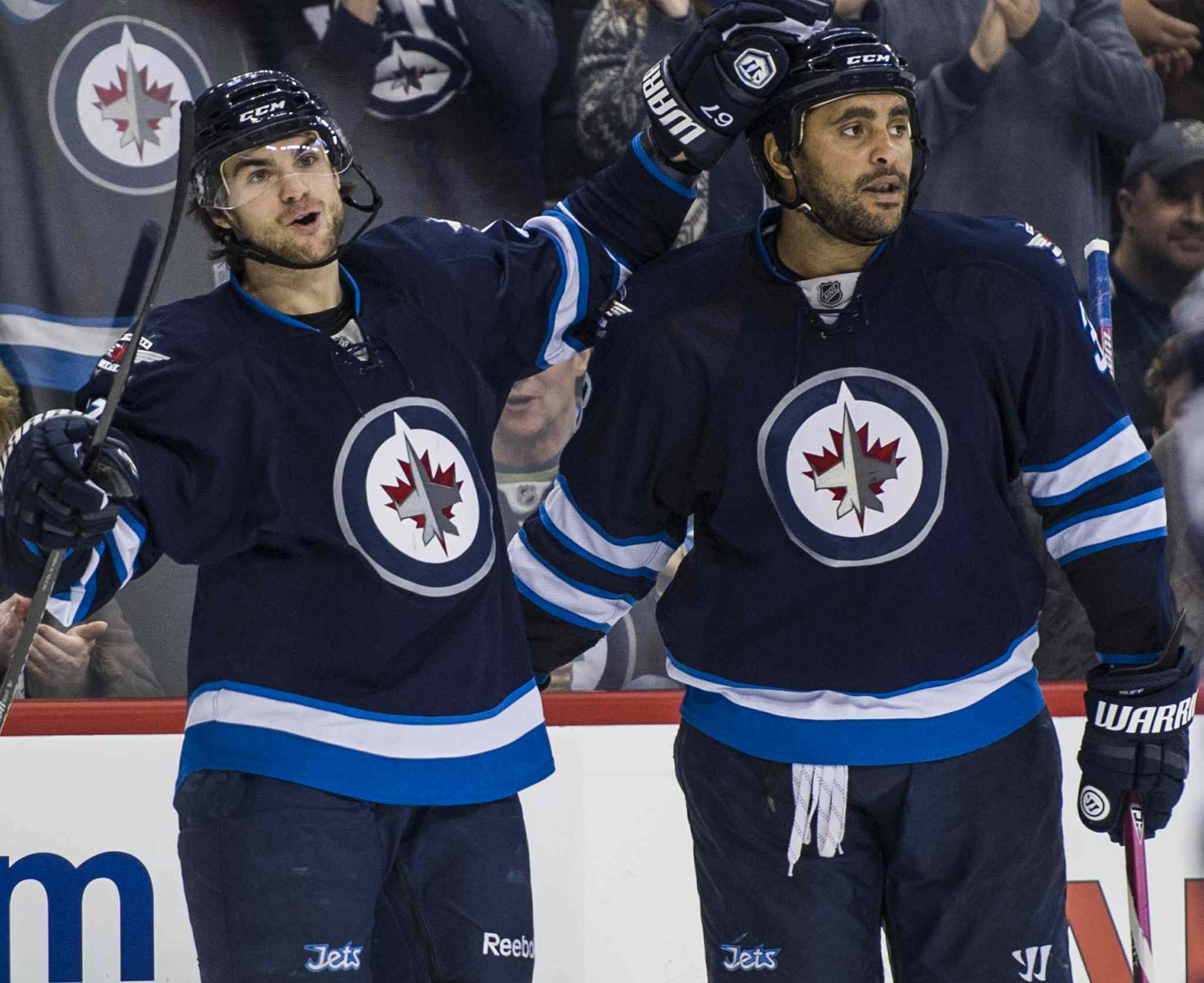Winnipeg Jets Michael Frolik (#67) celebrates his second period goal against the Florida Panthers with teammate Dustin Byfuglien (#33).