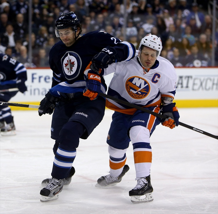 Eric Tangradi elbows New York Islanders' Mark Streit as they battle for the puck during the second period.