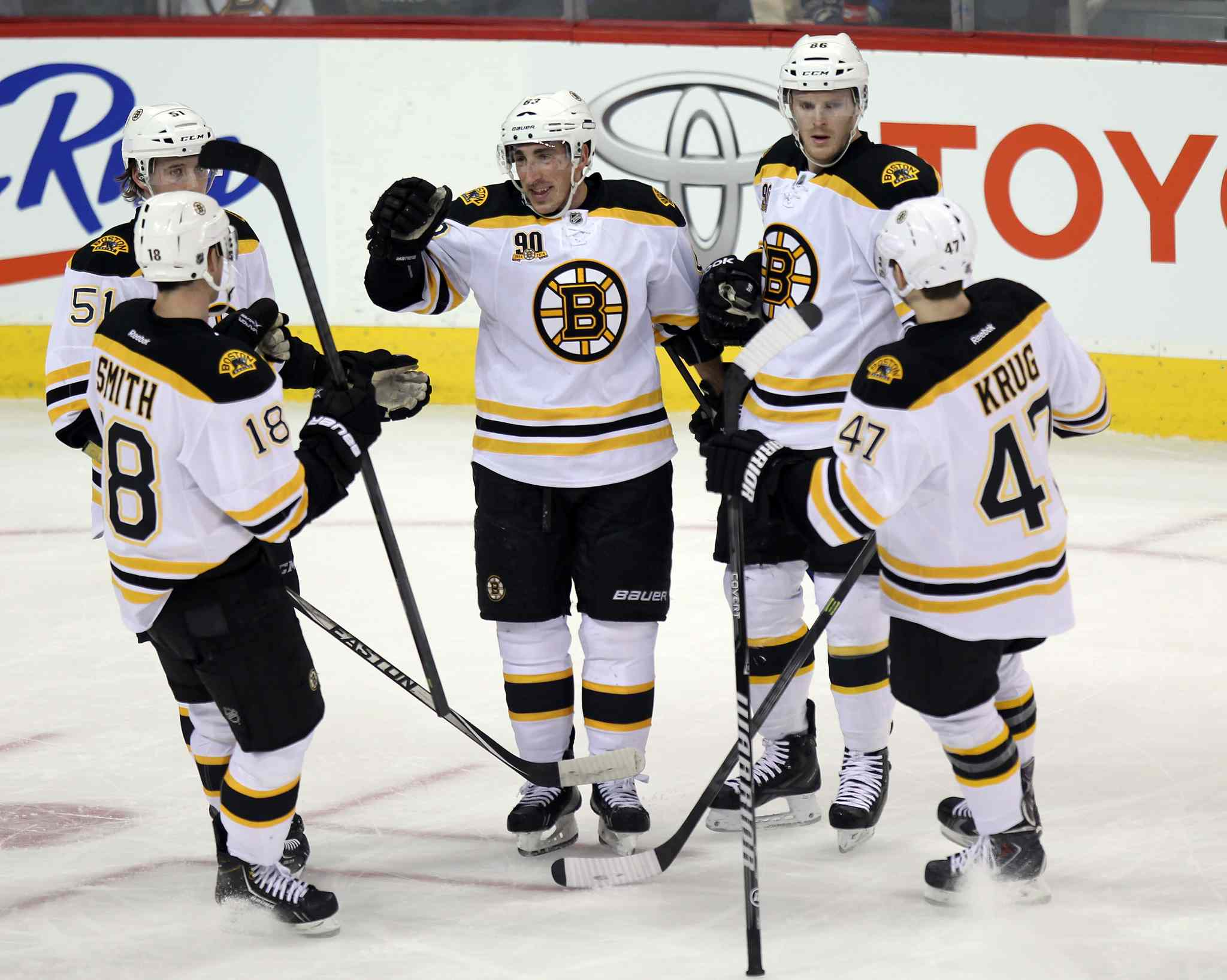 Boston Bruin linemates congratulate #63 Brad Marchand (centre) for scoring the Bruins' opener in the first period of Thursday's game.