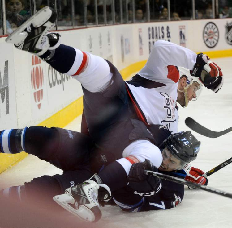 Washington Capitals' Mike Green lands on Winnipeg Jets' Scott Kosmachuk during pre-season NHL hockey action in Belleville, Ont., Saturday. (Sean Kilpatrick / The Canadian Press)
