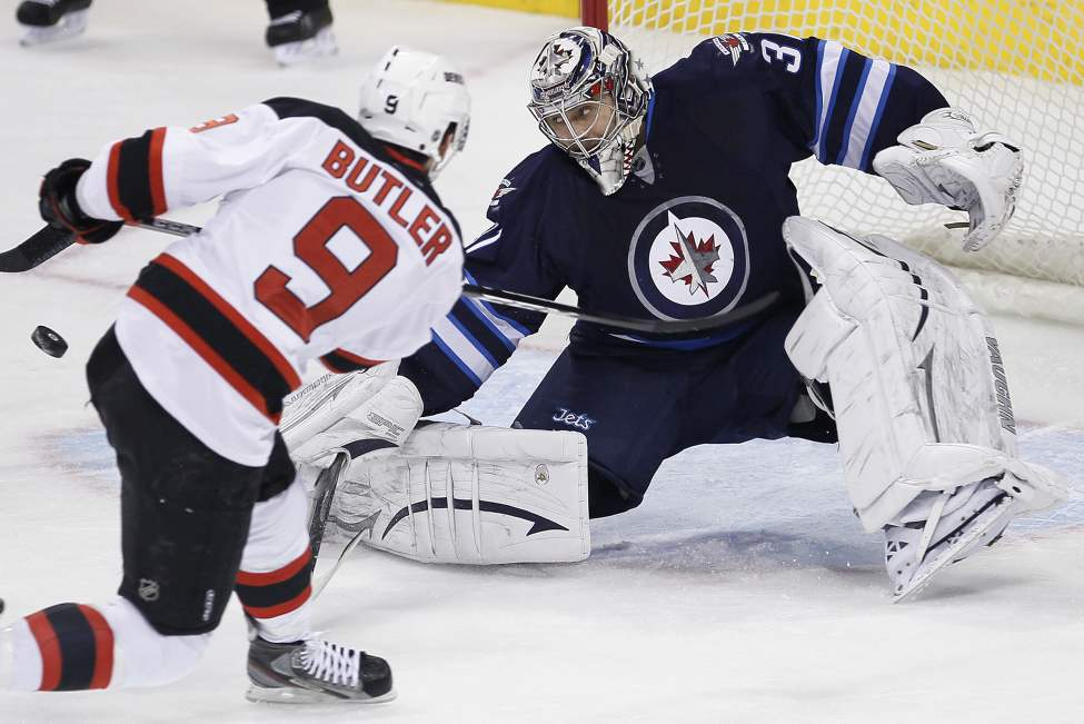 Winnipeg Jets goaltender Ondrej Pavelec (31) saves the shot from New Jersey Devils' Bobby Butler (9) during first-period NHL action in Winnipeg on Thursday, February 28, 2013.