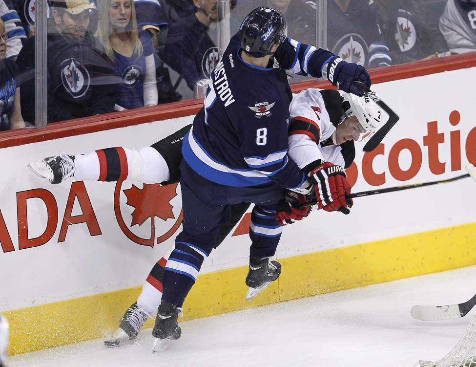 Winnipeg Jets' Alexander Burmistrov (8) takes out New Jersey Devils' Marek Zidlicky (2) during first period NHL action.