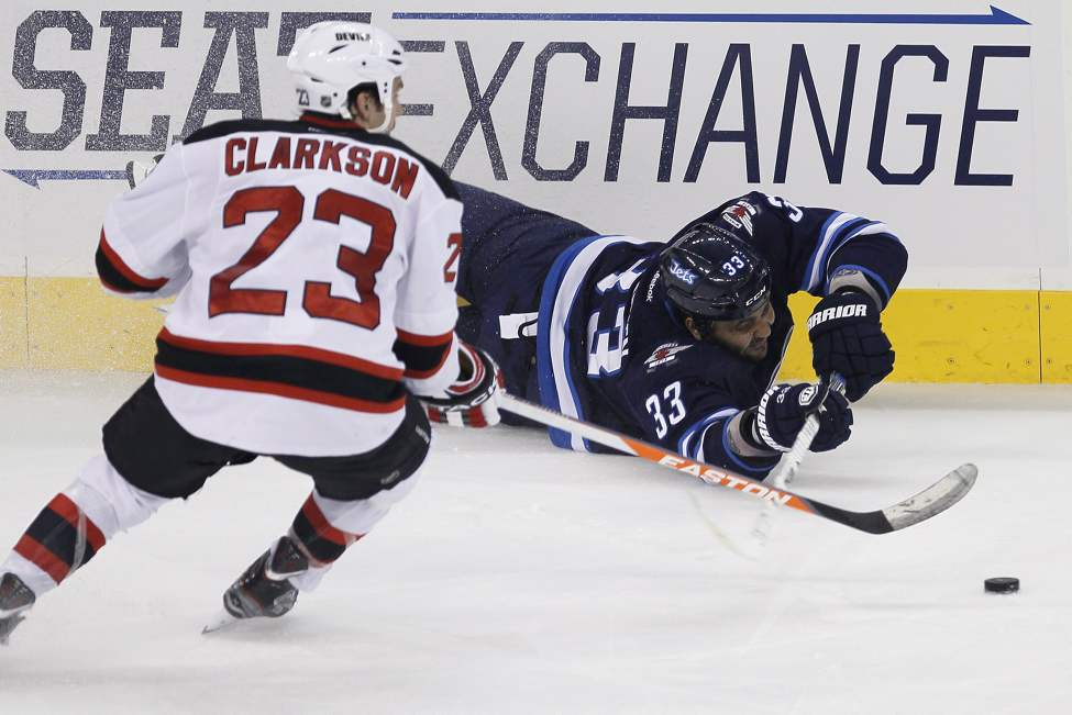 Winnipeg Jets' Dustin Byfuglien (33) plays the puck on the ice against New Jersey Devils' David Clarkson (23) during the third period. (THE CANADIAN PRESS/John Woods)