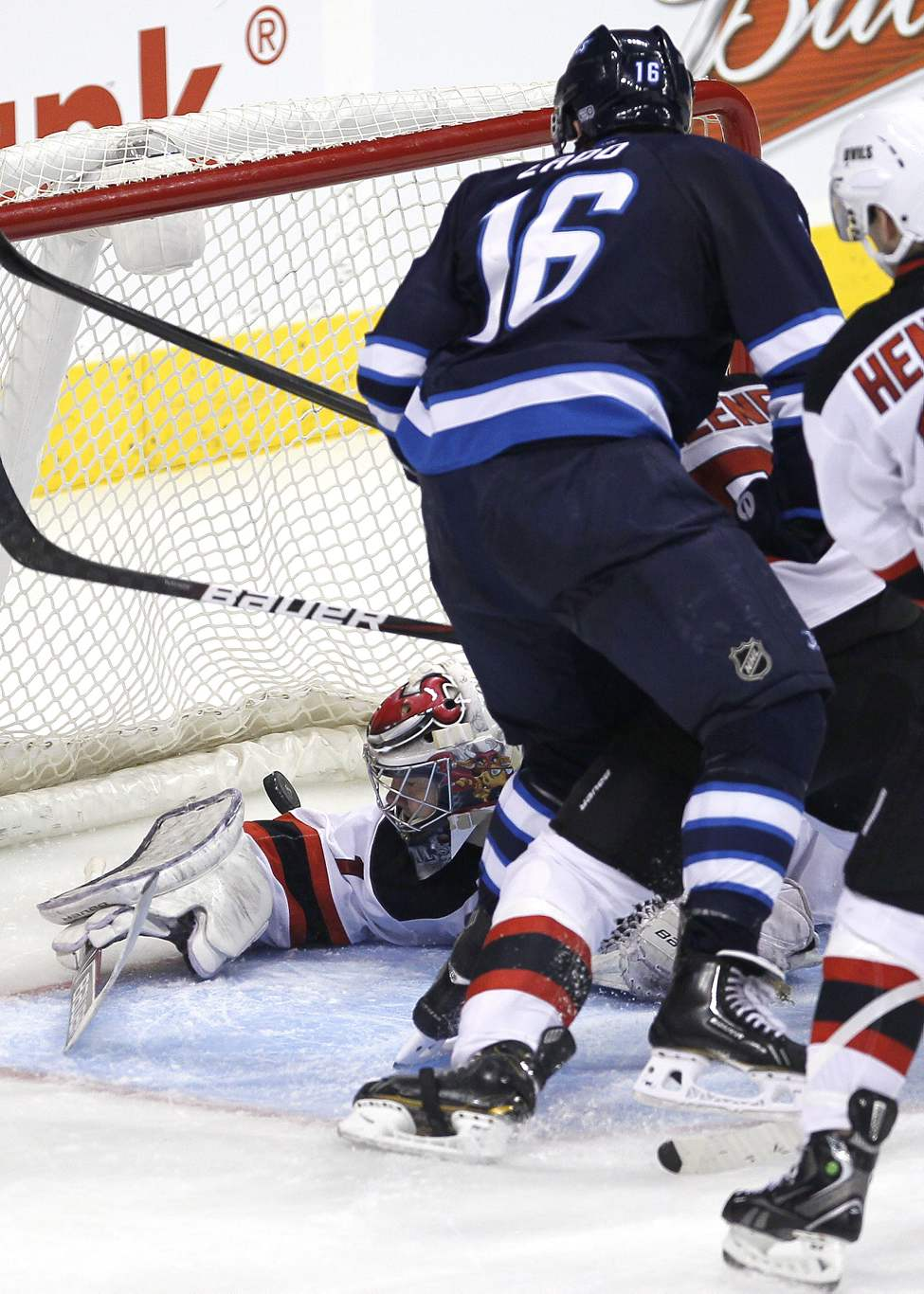 Winnipeg Jets' Andrew Ladd (16) scores his second goal against New Jersey Devil New Jersey Devils goaltender Johan Hedberg (1) during third period action.