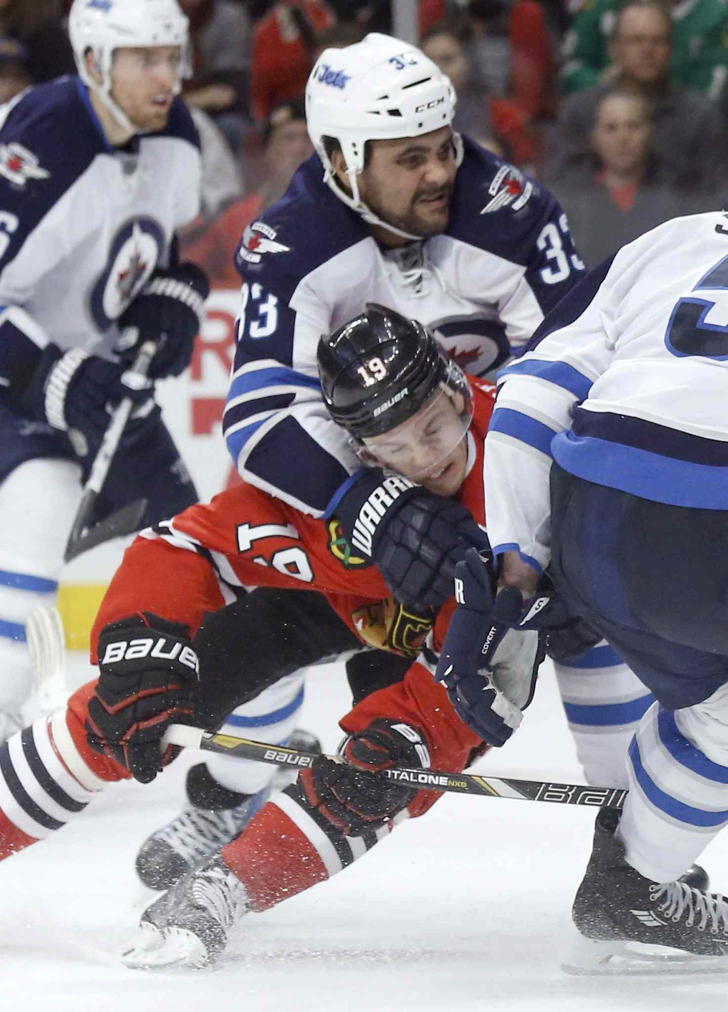 Jets forward Dustin Byfuglien subdues Blackhawks captain Jonathan Toews during the Jets' come-from-behind victory over the reigning Stanley Cup champs Sunday night in Chicago