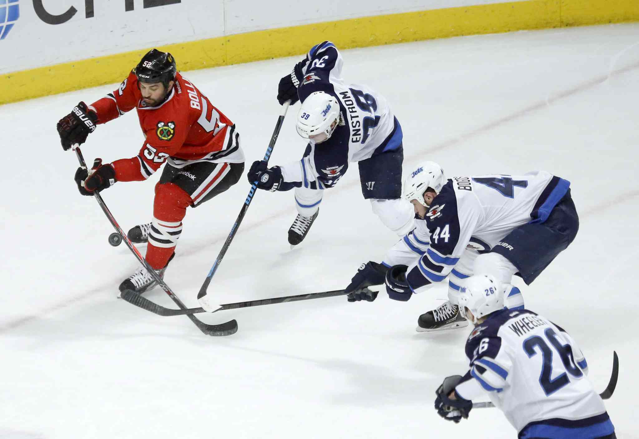 Blackhawks left wing Brandon Bollig can't get a shot-on-goal as Jets  Tobias Enstrom Zach Bogosian and Blake Wheeler close in.