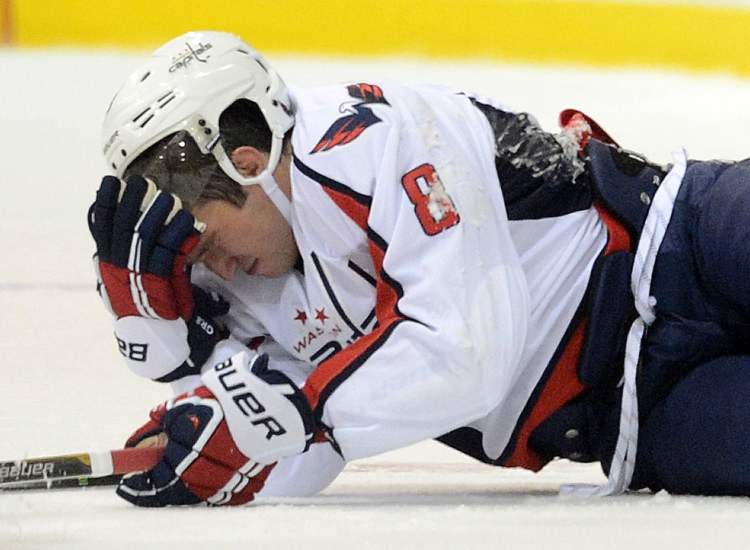 Capitals' captain Alex Ovechkin holds his head as he lies on the ice after taking a hit while playing the Winnipeg Jets during pre-season NHL hockey action in Belleville, Ont., on Saturday.