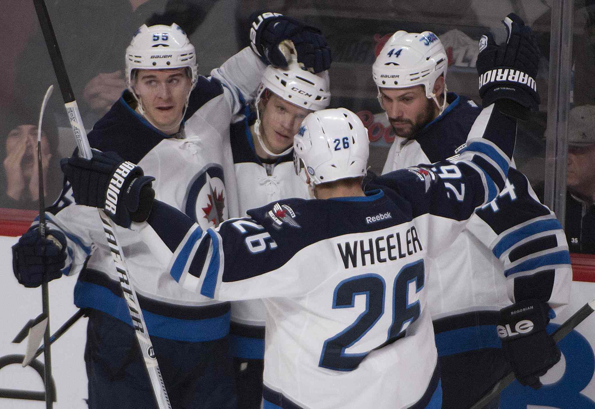 Winnipeg Jets' Tobias Enstrom, second from left, celebrates his second-period goal with Mark Scheifele (55), Blake Wheeler (26) and Zach Bogosian (44)after scoring against the Montreal Canadiens during the Jets 2-1 win in Montreal on Sunday.