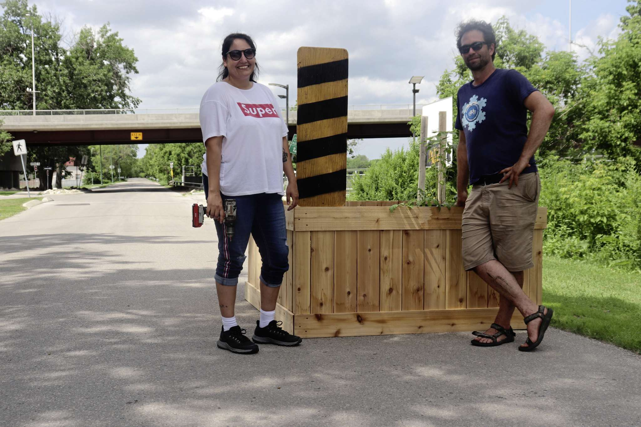 From left: Janell Henry, Healing Trails' program manager and Anders Swanson, Winnipeg Trails' executive director, standing beside one of the planter box traffic-calming devices.