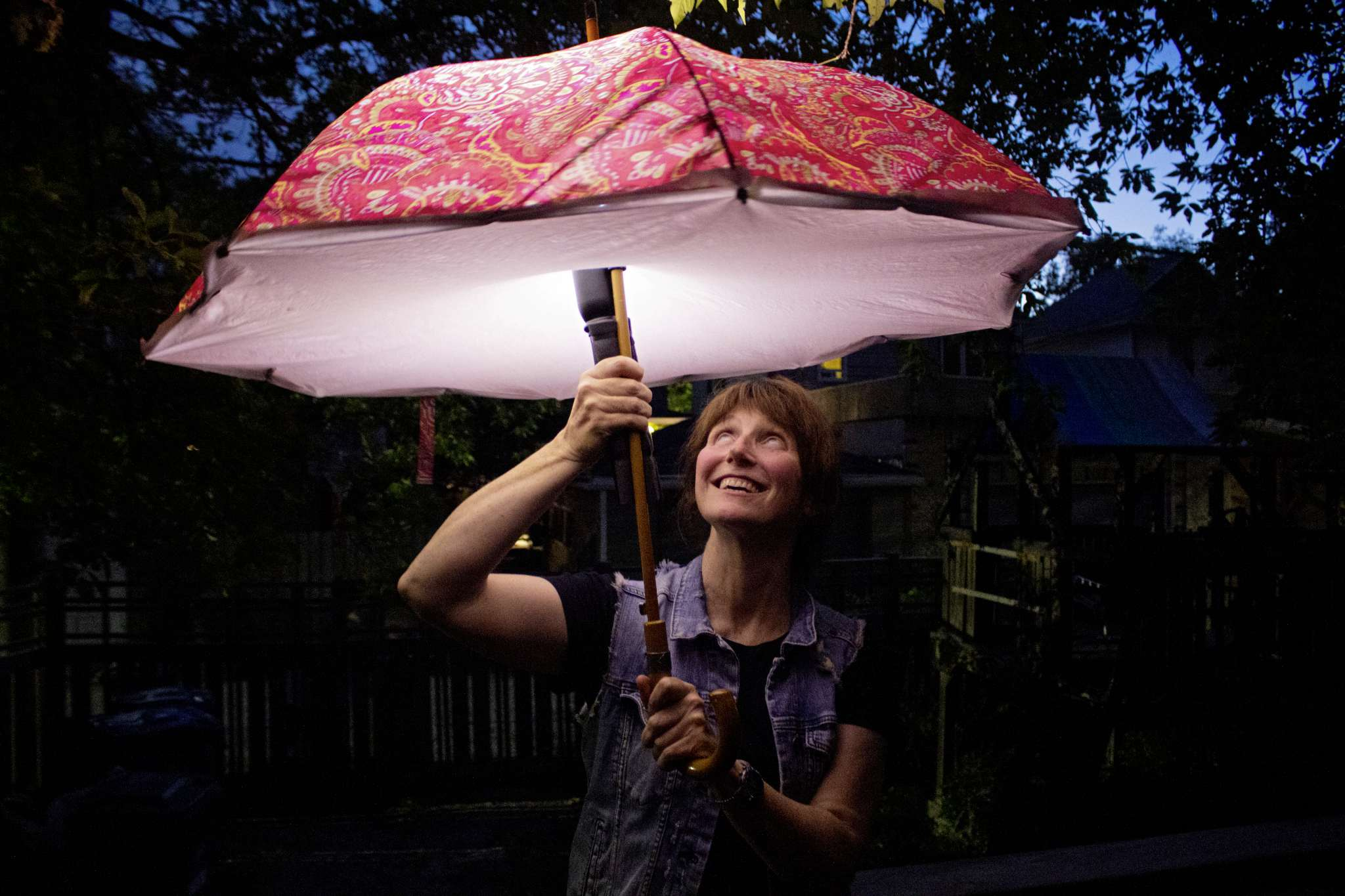 Linda Beech, holding up one of her light-up umbrellas at her Wolseley home. Beech is taking part in Nuit Blanche with her project Brolly Bright, where she plans to have five friends hold lit-up umbrellas and walk around downtown Winnipeg. The umbrellas are lit by high-powered flashlights.