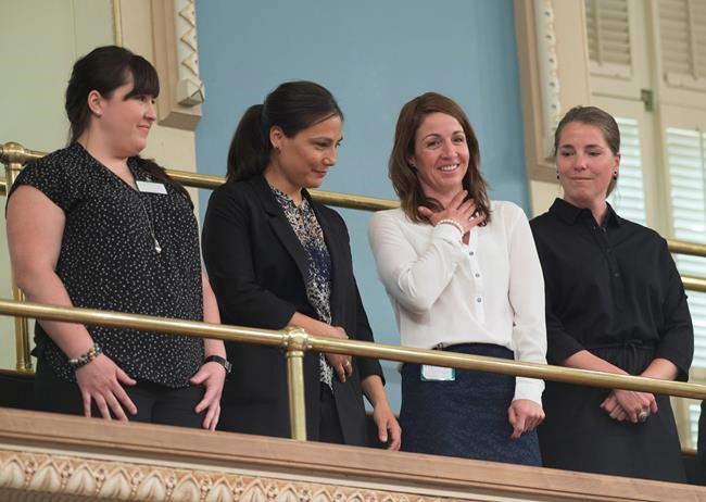 Former national ski team members Emilie Cousineau, from the left, Anna Prchal, Gail Kelly and Genevieve Simard stand as they are applauded for their courage after a motion by the National Assembly, Tuesday, June 12, 2018 at the legislature in Quebec City. THE CANADIAN PRESS/Jacques Boissinot