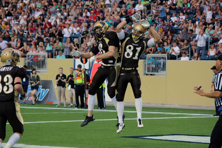 Manitoba Bisons wide receiver Andrew Smith (left) and slotback Christian Hansen celebrate a touchdown against the UAlberta Bears to the cheers of fans at Investors Group Field Aug.30.
