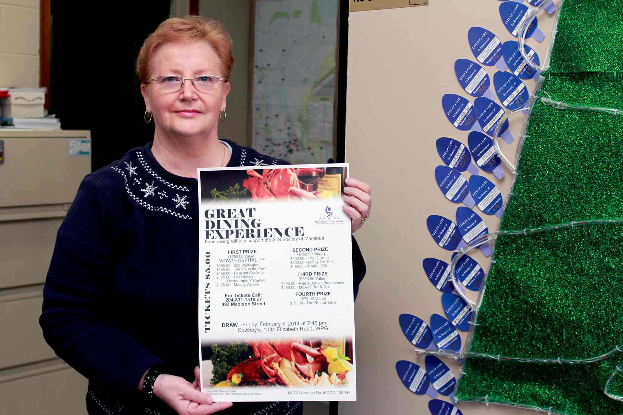 ALS Society of Manitoba executive director Diana Rasmussen holds up a poster with details about the Great Dining Experience. Tickets can be bought at the society's head office at 493 Madison Ave., St. Vital Shopping Centre, and Garden City Shopping Centre.