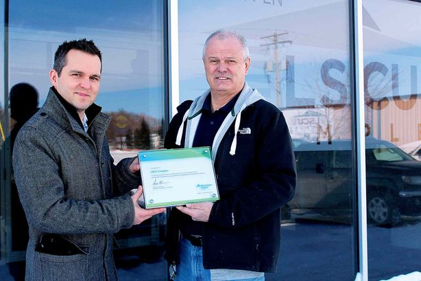 (Left) Manitoba Hydro's New buildings program co-ordinator Cory Young presents a plaque to recreation director Tom Cardinal recognizing the new LSCU Complex in La Salle as a Power Smart facility.