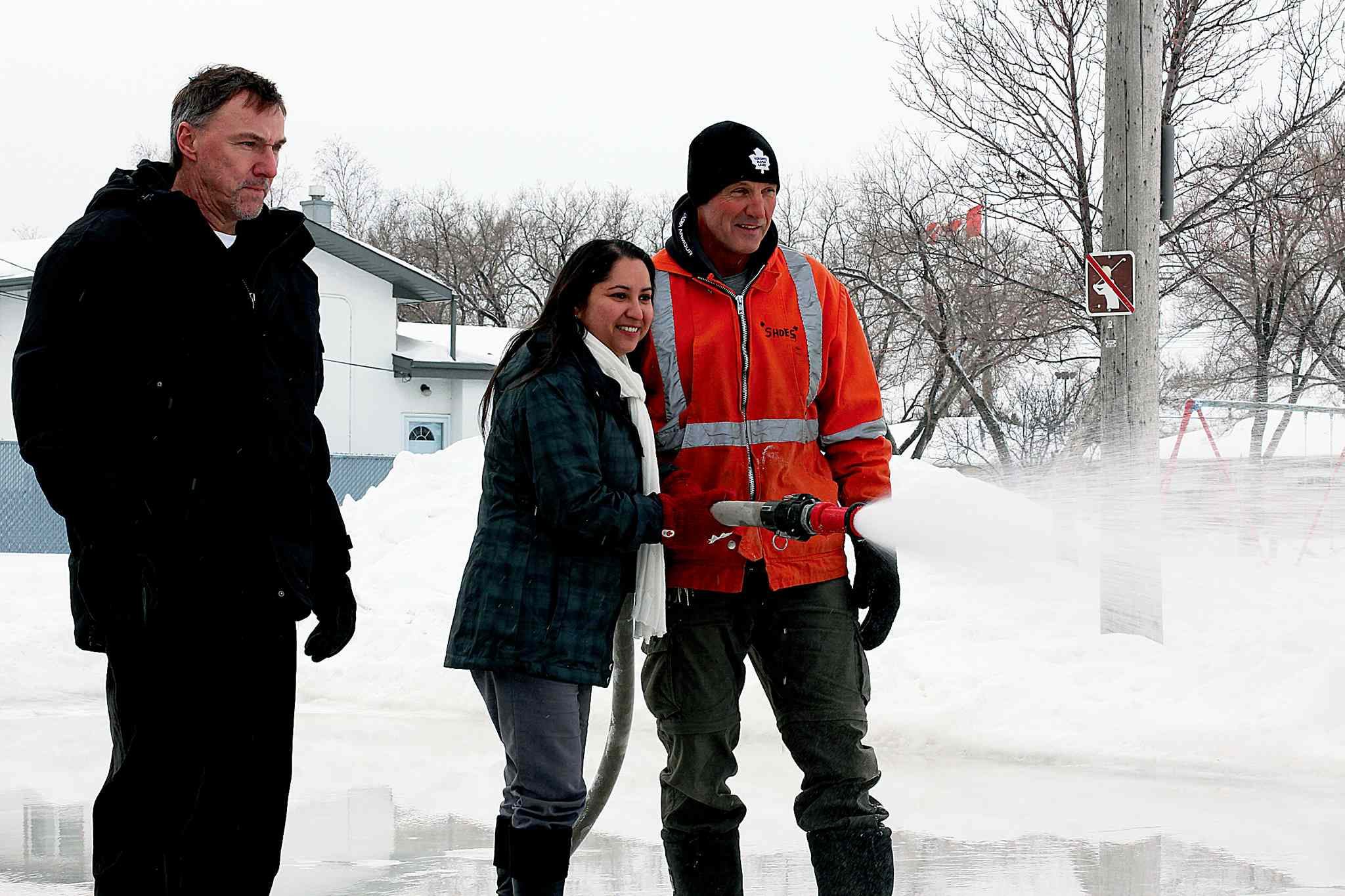 (From left) Jack Lubinski, superintendent with Parks North; Devi Sharma, city councillor for Old Kildonan; and Bill Hasiuk, parks worker, help flood a recreational skating rink at Gilia Park in Garden City.