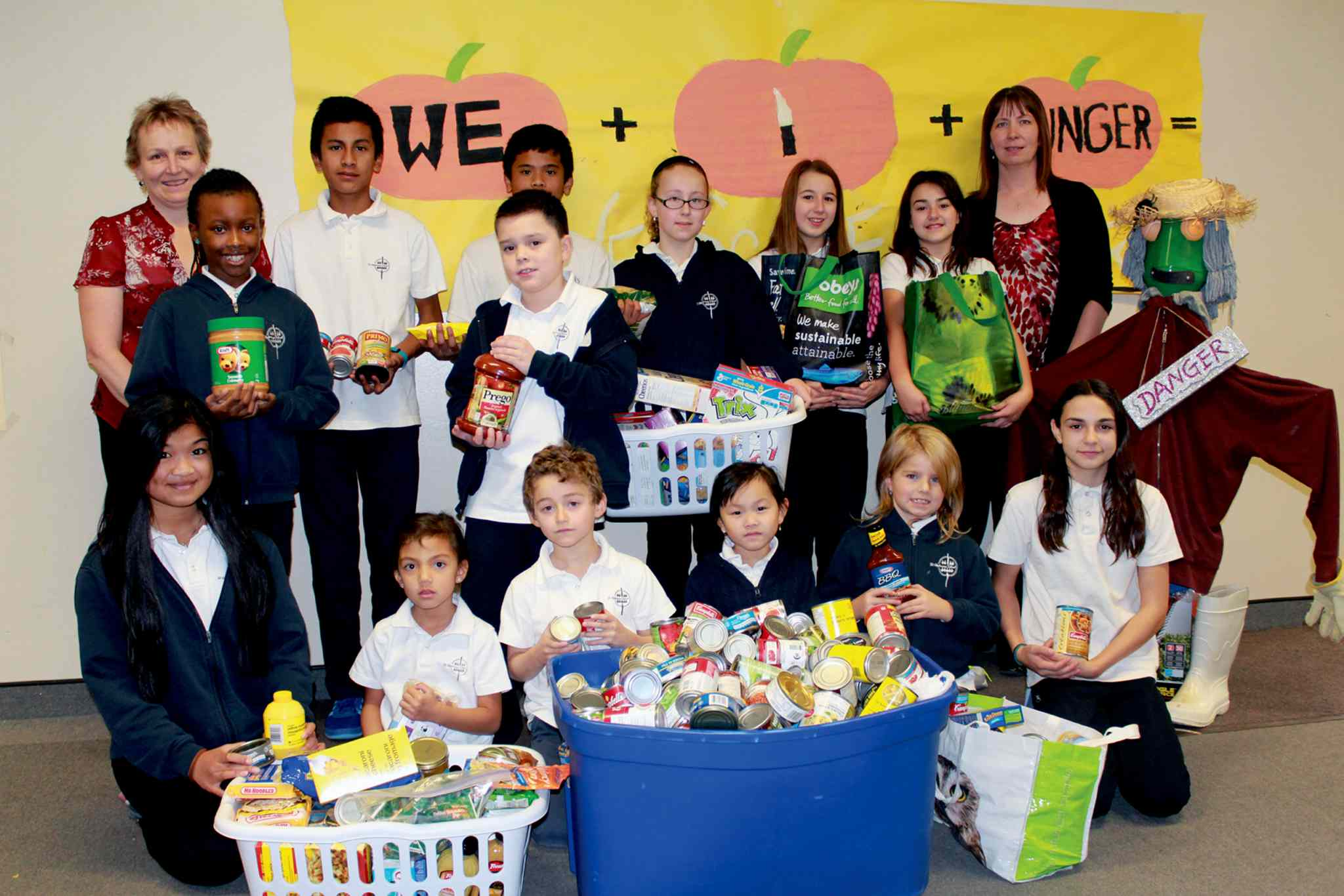 St. Alphonsus School principal Christine McInnis (back left) and secretary Patti Resendes (back right) with a handful of students who helped compile a shipment of non-perishable food for the K-8 school's We Scare Hunger campaign.