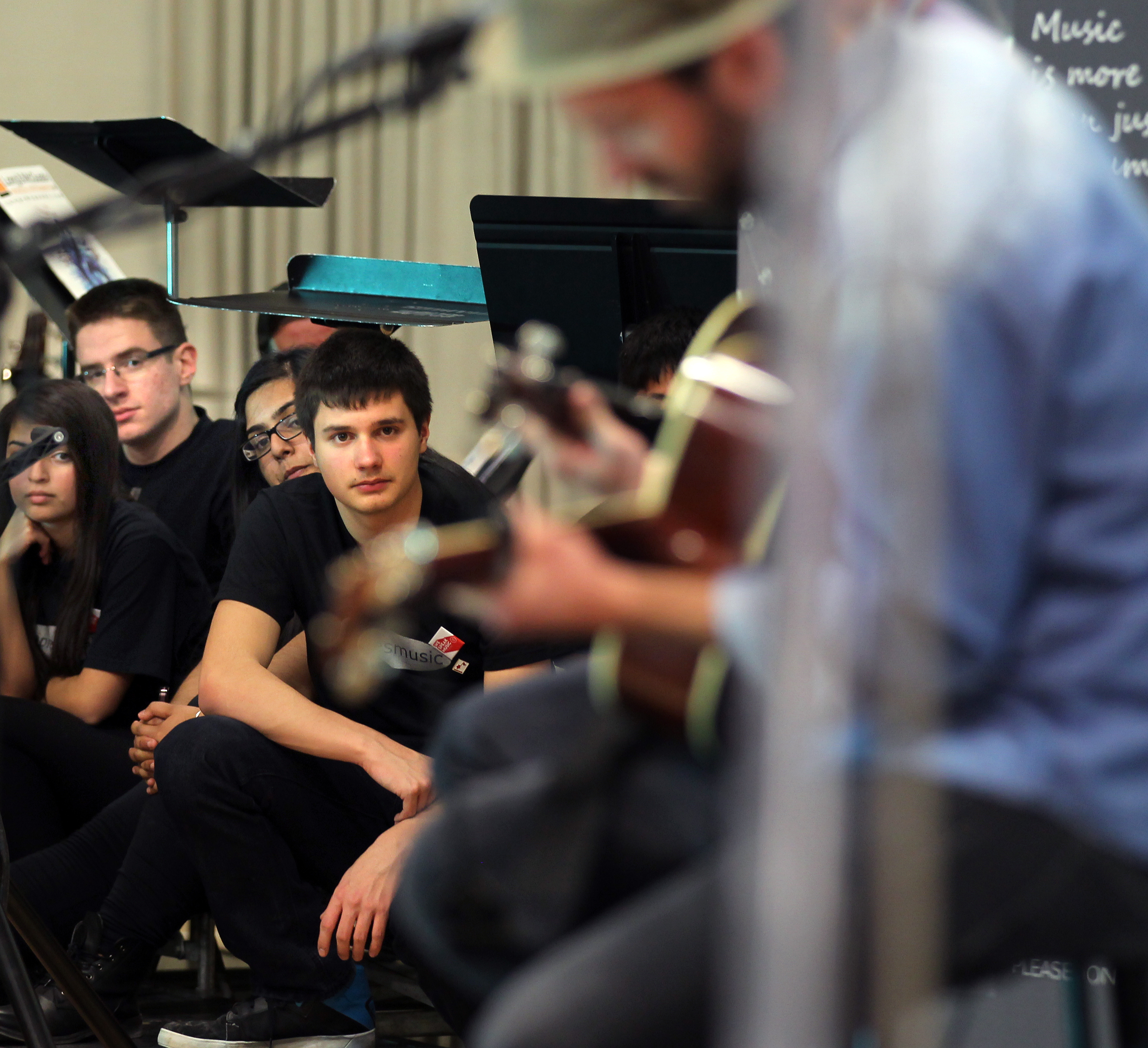 Musicians from the Maples Collegiate Jazz Band peer out from underneath their music stands while they follow the Trews in a concert and presentation at Maples Collegiate Friday afternoon.