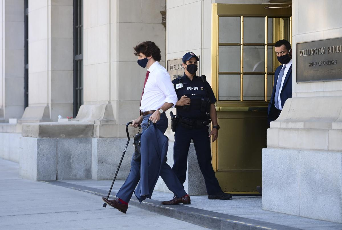 Prime Minister Justin Trudeau walks with a cane as he leaves a news conference in Ottawa on May 31, 2021. Trudeau twisted his ankle while playing Frisbee with his kids.