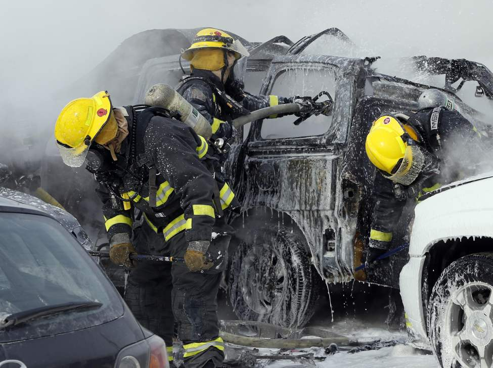 Fire fighters tend to three cars damaged by an explosion that ripped the roof from a van carrying a propane tank in parking lot of Super Store on Sargent Avenue at St. James Street. March 3, 2014 (KEN GIGLIOTTI / WINNIPEG FREE PRESS)