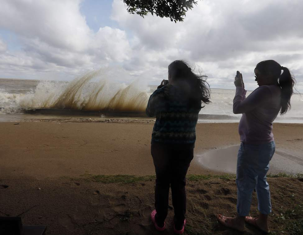 Freya Croatto, left, and Alana Hing take pictures of crashing waves at  Winnipeg Beach. High winds caused water to crash over the break wall to the boardwalk and bike path. July 14, 2014  (KEN GIGLIOTTI / WINNIPEG FREE PRESS)