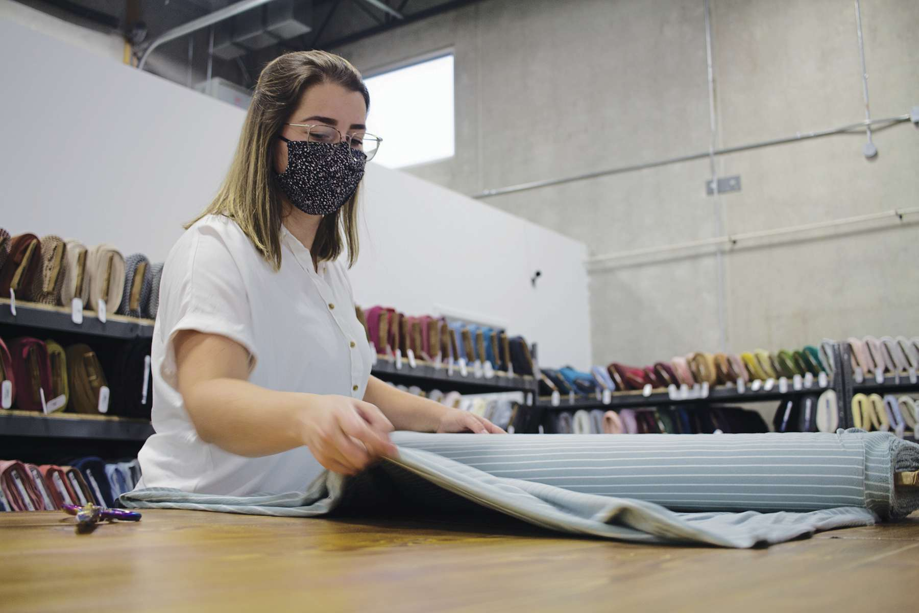 Brianne Davison, manager of The Fabric Snob, measures and cuts from a roll of fabric at the Manitoba business's new retail location in Oak Bluff.