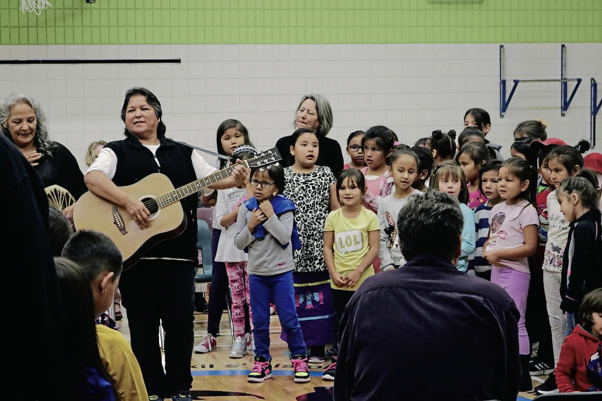 Kids sing in Ojibwa, led by their teacher Gloria Barker (left, with guitar) at the Riverbend Community School Assembly on Sept. 13.