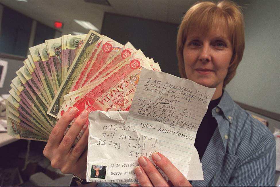 Lindor Reynolds holds $2,000 that was sent to the Free Press for a Christmas donation in 1998 by Mrs. Annonomous. The envelope broke open at the post office and an employee there made sure all the money got to the Free Press.  (BORIS MINKEVICH / WINNIPEG FREE PRESS)