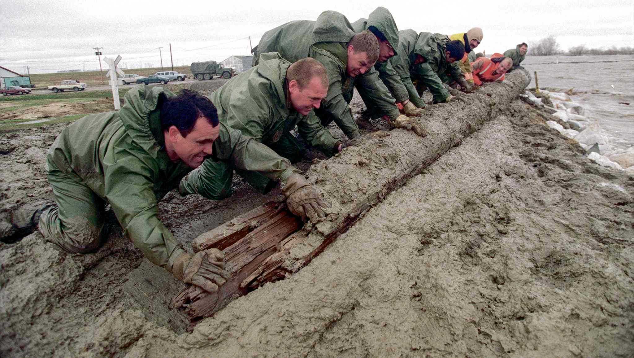 Members of Calgary's First Battalion, PPCLI battled 80 km/h winds in St Jean Baptist as they scrambled to reinforce the town's protective earthen dike. At risk of erosion from the pounding waves, the soldiers pushed logs and sandbags into the swollen Red River to act as a breakwater and a means of a protection for the structure. Moisture from the waves turned the mostly clay dikes into a mud pit, making the work nearly impossible.